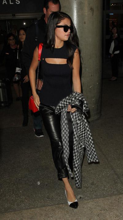 Селена Гомес в аэропорту в кожанных брюках капри, черный топ с вырезом и серый плащ в клтку