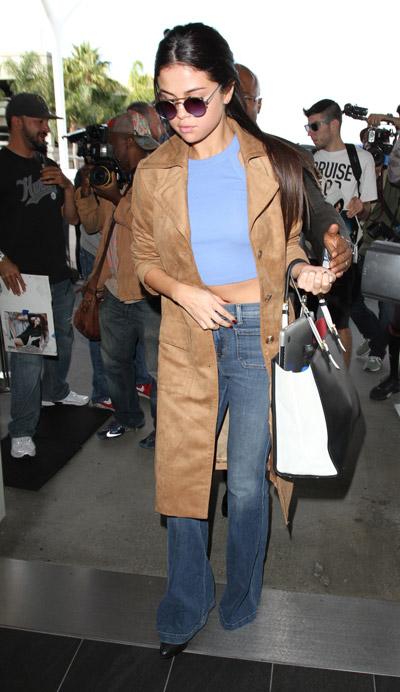 Селена Гомес в синих расклешенных джинсах, голубом топе и коричневый длинный плащ