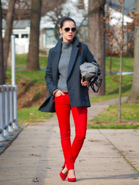 Девушка в сером пальто и красных брюках