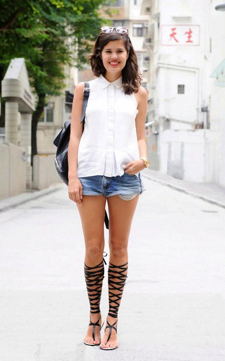 Девушка в джинсовых шортах, белой блузке и гладиаторах