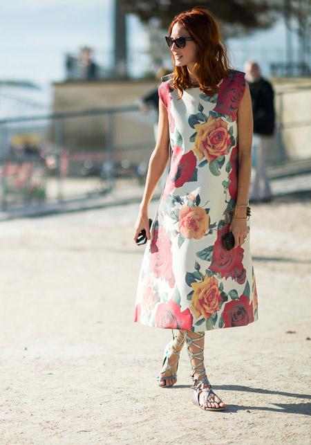 Девушка в прекрасном платье с цветочным принтом и гладиаторах