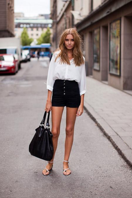 Девушка в белой рубашке, черных шортах и сандалиях