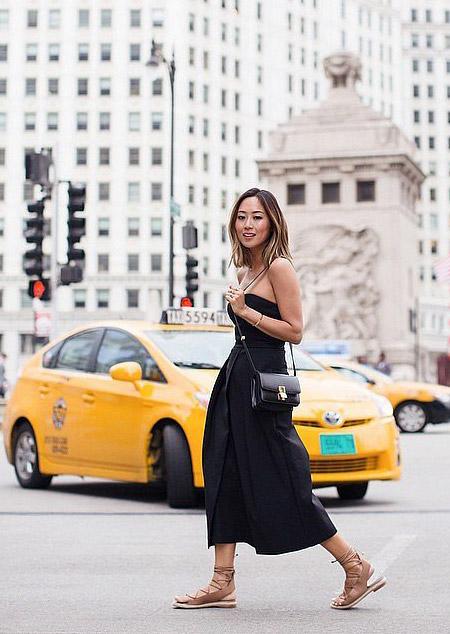Девушка в длинном черном платье и сандалиях