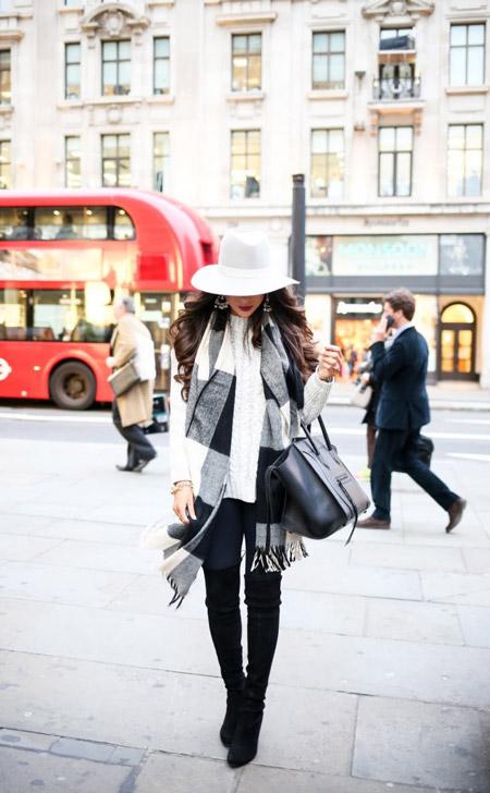 Девушка в белоснежной шляпе, черных сапогах выше колен, легинсы и шарф в клетку