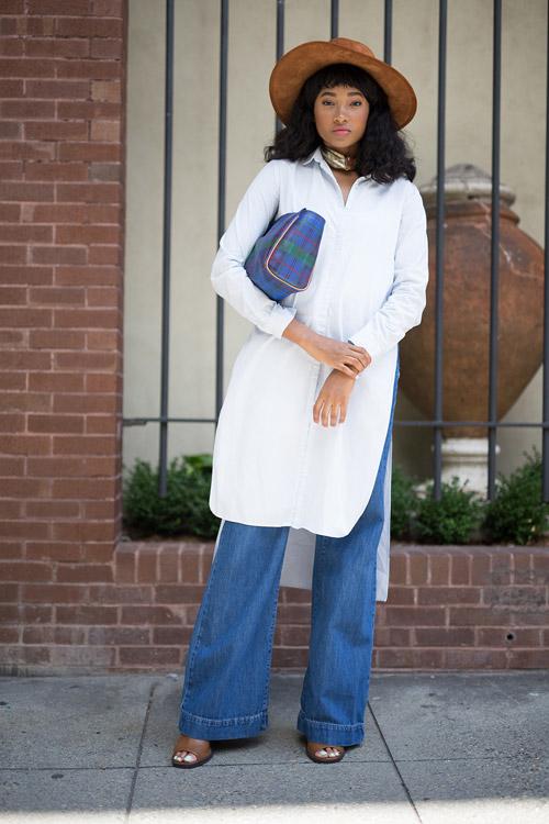 Девушка в белой платье рубашке, шляпе и широких джинсах