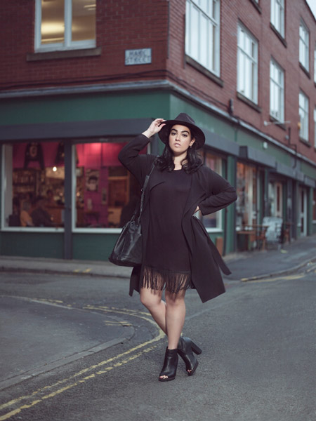 Девушка в черной шляпе, пальто и черное платье с бахромой на подоле