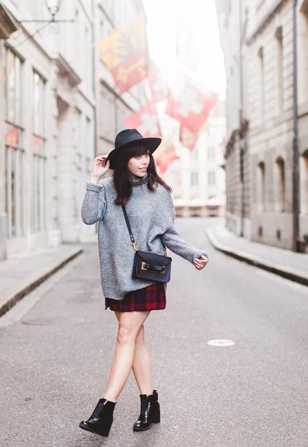 Девушка в черной шляпе, серый свитер и красная юбка