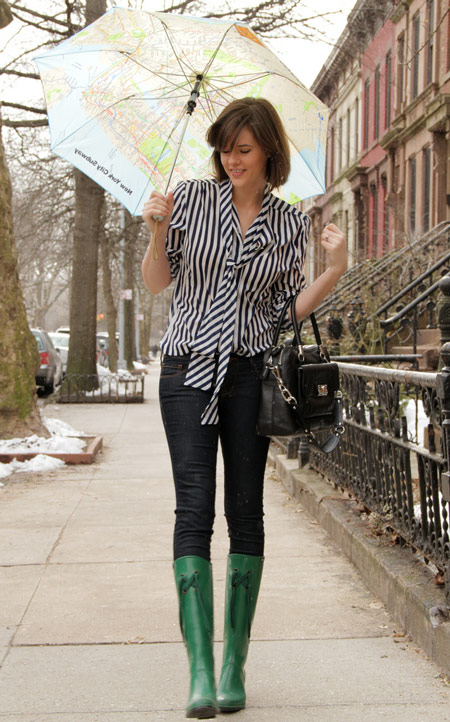 Девушка в черных брюках и зелёных сапогах