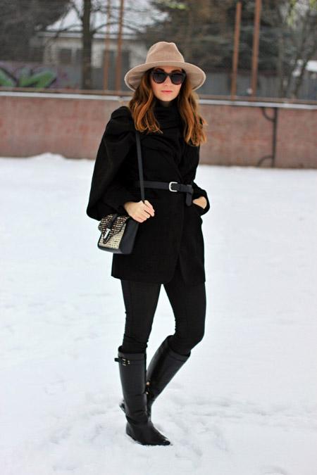 Девушка в черных сапогах и пальто с ремнем на талии, бежевая шляпа