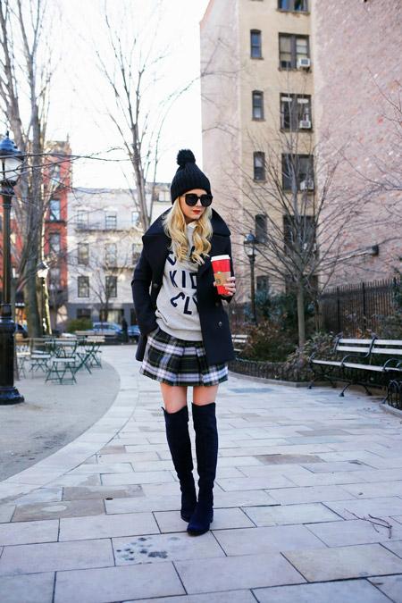 Девушка в черных высоких сапогах, клетчатой мини юбке, свишоте, укороченном пальто, черная шапка с помпоном
