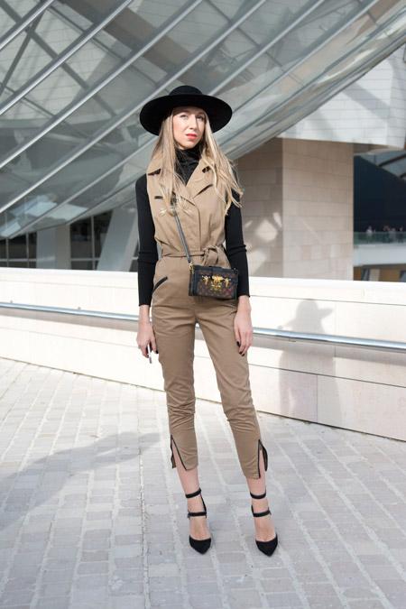 Девушка в комбинезоне песочного цвета, черной водолазке, шляпе и туфлях