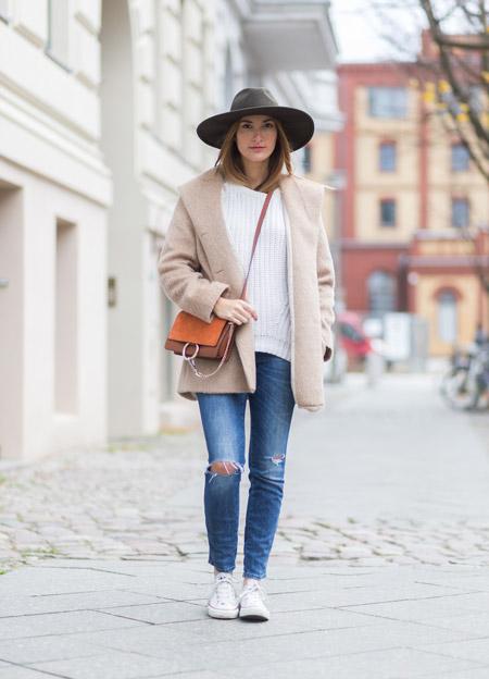 Девушка в коричневой шляпе, синих рваных джинсах с кедами, бежевое пальто и белый свитер