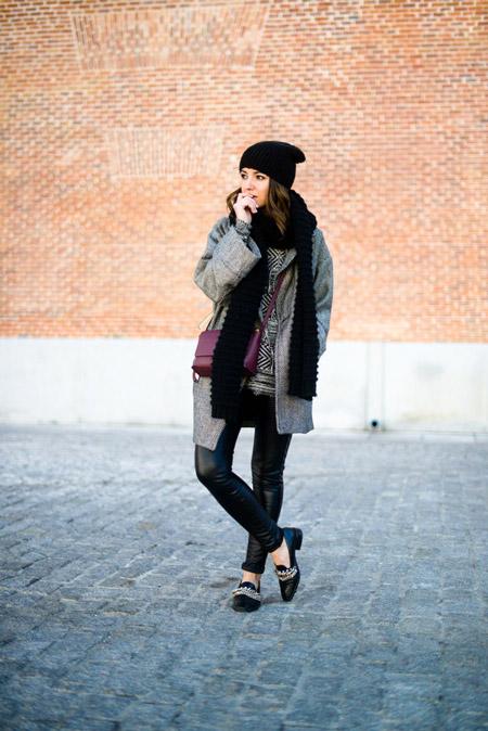 Девушка в кожанных лосинах, серое прямое пальто и черная вязаная шапка и шарф