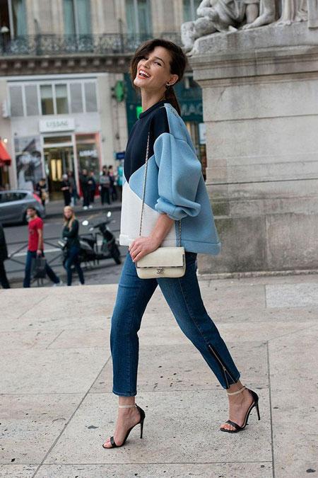 Девушка в объемном свитшоте и джинсах