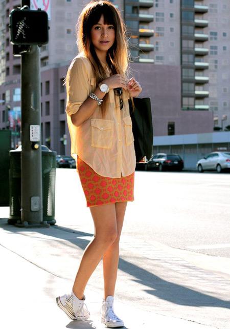 Девушка в оранжевой юбке и кедах
