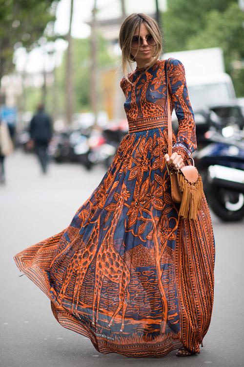 Девушка в разрисованном платье в пол и с сумкой с бохромой