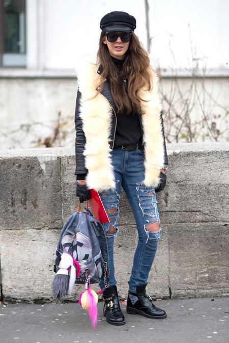 Девушка в рваных джинсах, кожаной куртке с белой меховой жилеткой и черная кепи