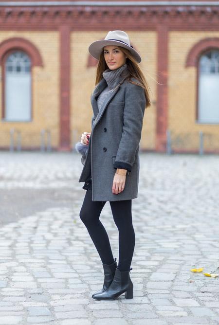 Девушка в серой шляпе, пальто прямого покроя и серый свитер с большой горловиной
