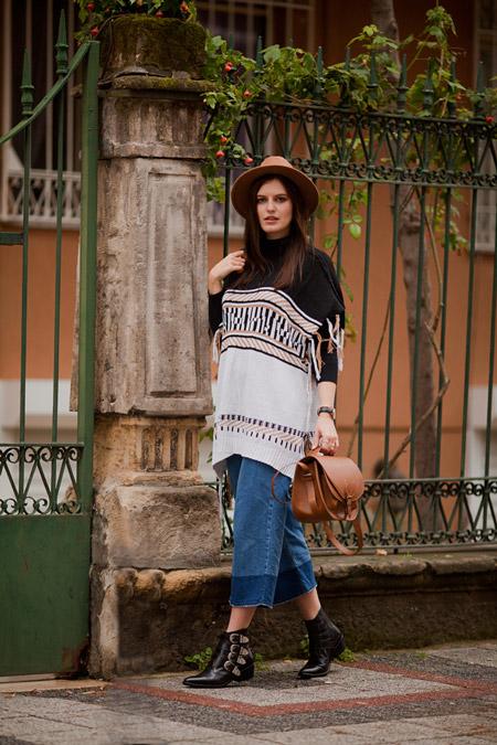 Девушка в шляпе песочного цвета, черно-белой накидке и широких джинсах