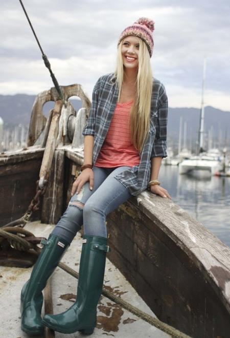 Девушка в зеленых сапогах и голубых джинсах