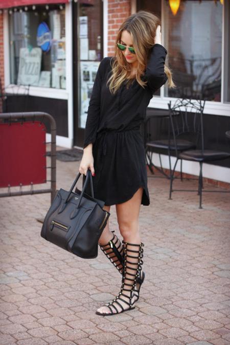 Девушка в легком черном платье и черных гладиаторах