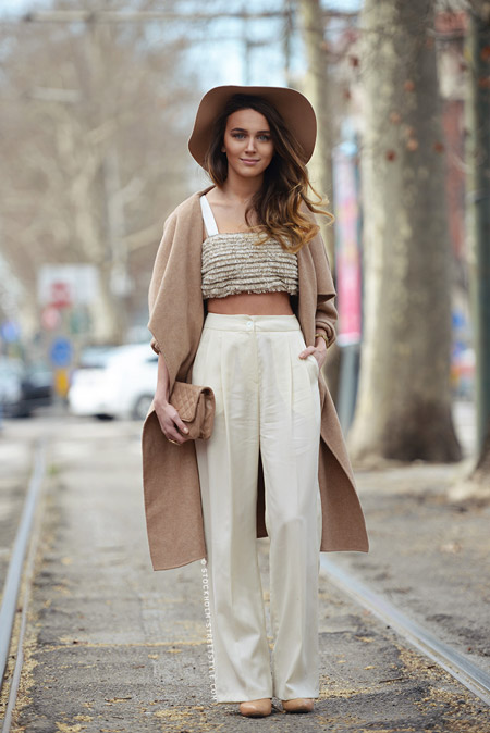 Модель в бежевой шляпе и пальто, белые широкие штаны и кроп топ