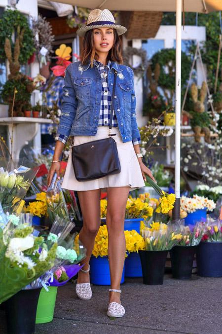 Модель в бежевой шляпке с синей лентой, мини юбке, рубашке в бело-синию клетку и джинсовке