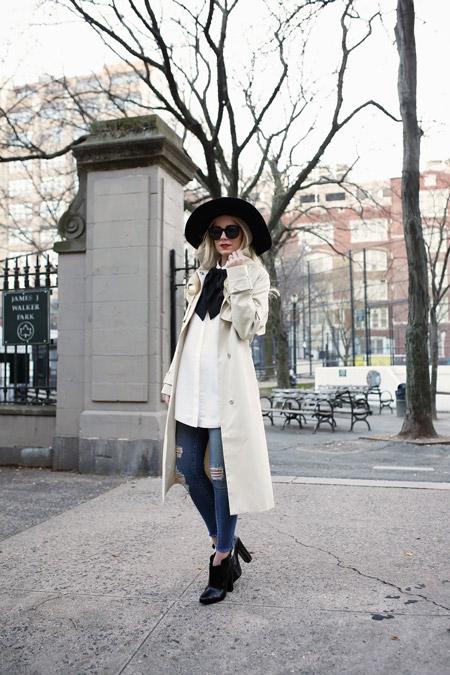 Модель в черной шляпе, белая блуза с черным бантом, светлый плащ и рваные джинсы