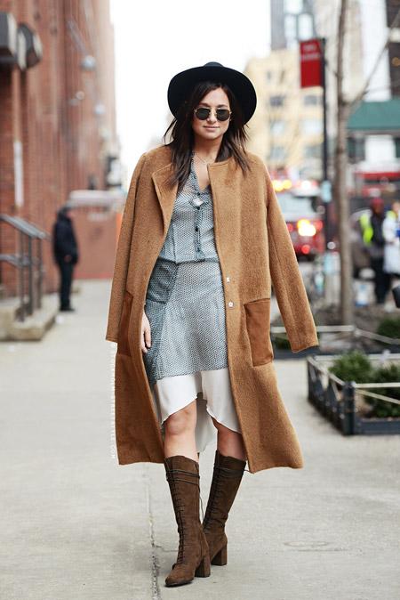 Модель в черной шляпе, пальто песочного цвета, серое платье и коричневые замшевые сапоги