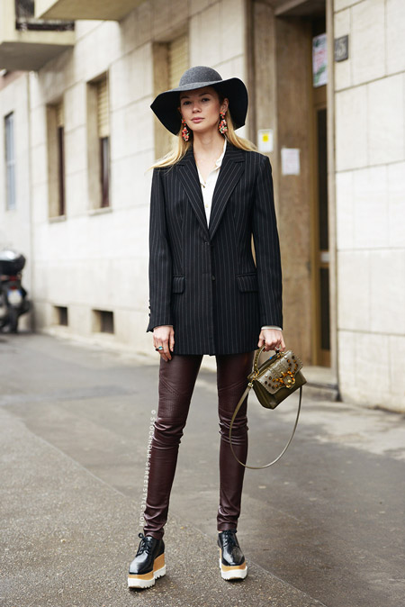 Модель в черной шляпе, пиджак с вертикальной полоской и коричневые кожанные лосины