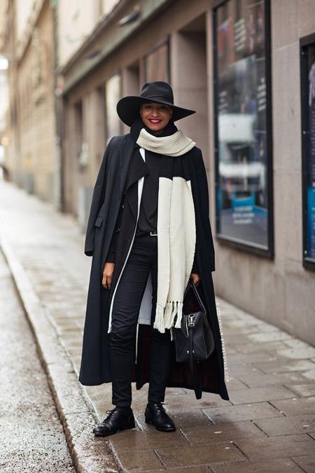 Модель в черной шляпе, плаще, зауженных брюках и черно-белый палантин