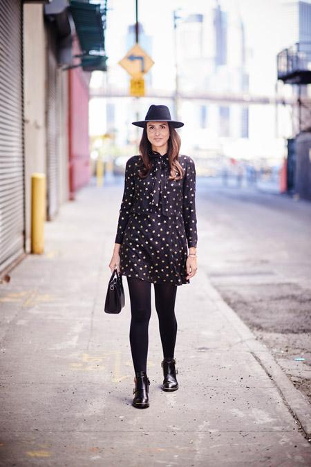 Модель в черной шляпе, плотных колготках и легкое шифоновое платье с принтом