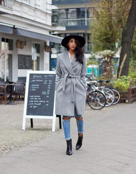 Модель в черной шляпе, сером пальто с поясом и рваных голубых джинсах