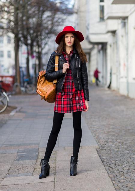Модель в красной шляпе, плотных колготках, куртка косуха и красное платье в клетку