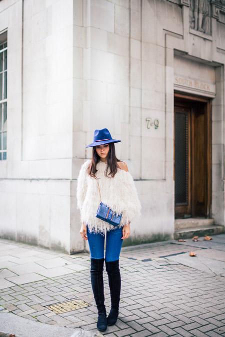Модель в синей шляпе, черных сапогах выше колен, джинсы с обтяжку и белая блуза с бахромой