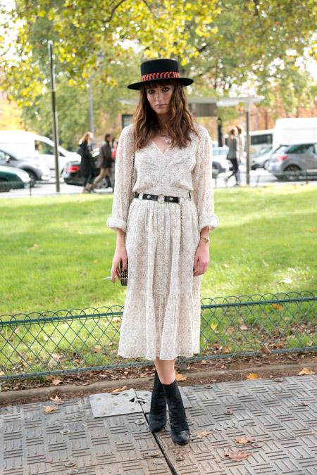 Модель в светлом летнем платье с поясом, черная квадратная шляпа и ботильоны