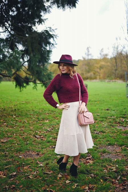 Модель в светлой юбке миди, бордовый свитер и бордовая шляпа
