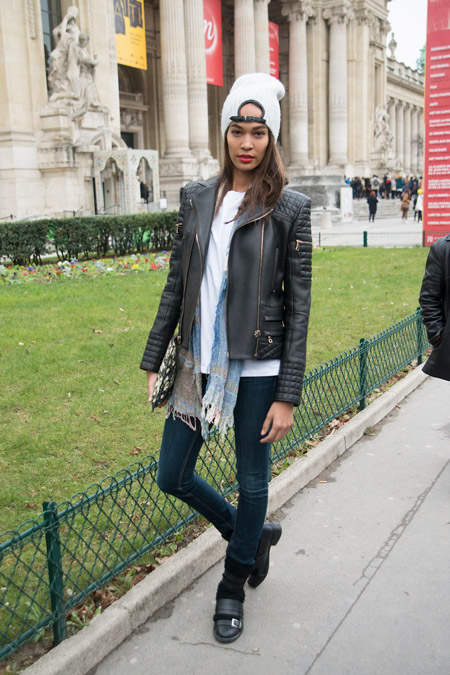 Модель в зауженных темных джинсах, куртка косуха, белая футболка и серая шапка