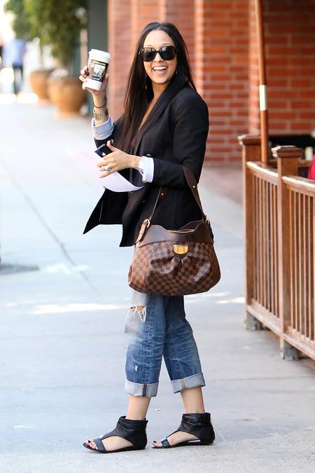 Девушка в джинсах, жакете и черных сандалиях
