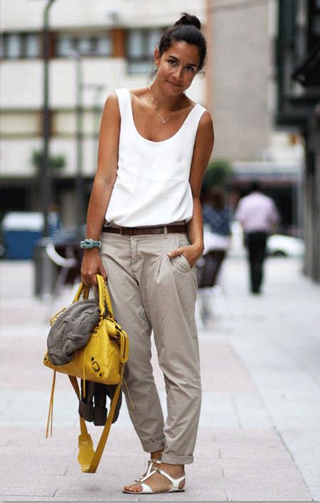 Девушка в серых брюках, майке и сандалиях