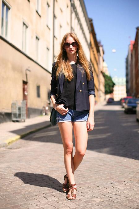 Девушка в джинсовых шортах, сандалиях и жакете