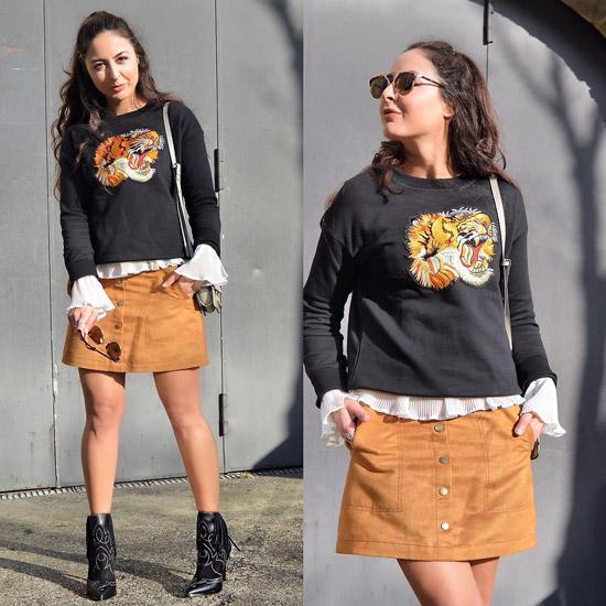 Девушка в мини юбке и свитере с принтом