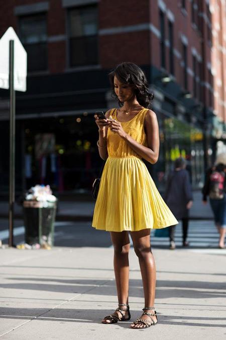 Девушка в желтом платье и серых сандалиях