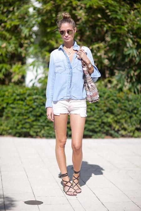 Девушка в белых шортах, джинсовой рубашке и сандалиях