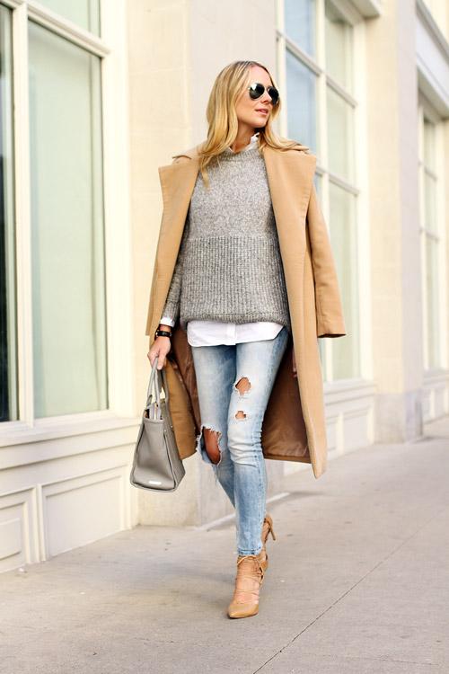 Девушка в рваных джинсах и сером свитере
