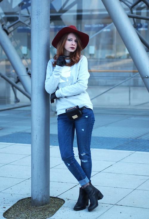 Девушка в джинсах, сером свитшоте и шляпе