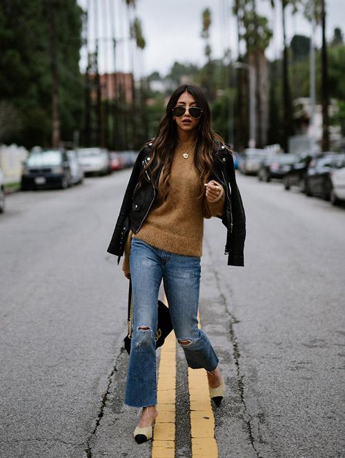 Девушка в джинсах клеш, свитере и кожаной куртке