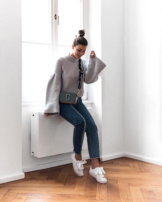 Девушка в джинсах, свитере с широкими рукавами и кроссовках