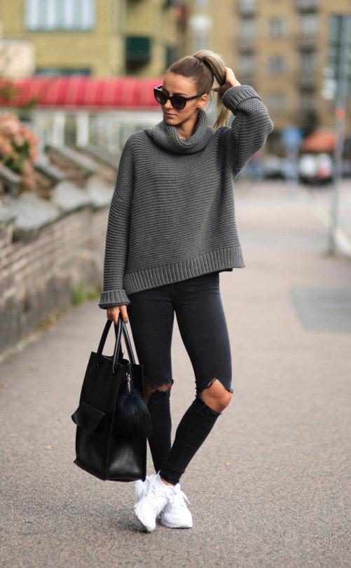 Девушка в свитере и джинсах с рваными коленками