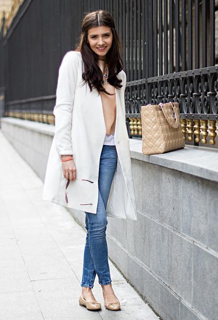 Девушка в белом плаще и джинсах